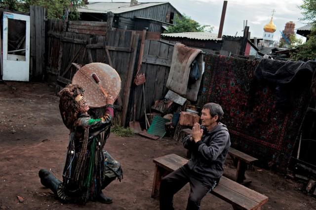 Šaman Adygži po zádušním obřadu očišťuje muže na dvorku jeho domu – přímo vedle rozestavěného pravoslavného chrámu. Kyzyl.